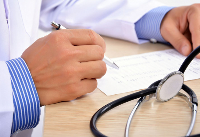 Médecin installé à son bureau en train de relire un document